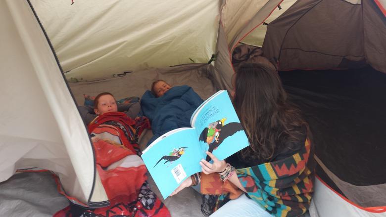 Les enfants, dans la tente et au chaud dans le duvet, écoute une histoire.